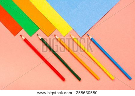 Sheets of colored cardboard and colored pencils on a red background. Top View stock photo