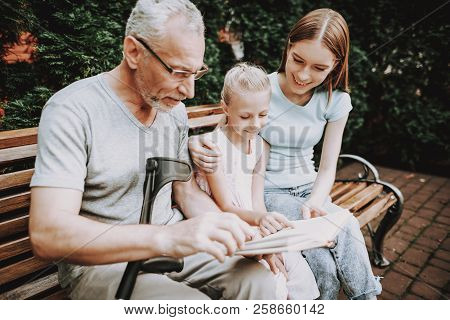Book on Bench with Old Man. Businessman with Girls reed Book in Bench. Family spend Time Toggether. Rehab with Family and Young Nurse. Medicine and Help Family. Elderly with Happy and Young Woman. stock photo