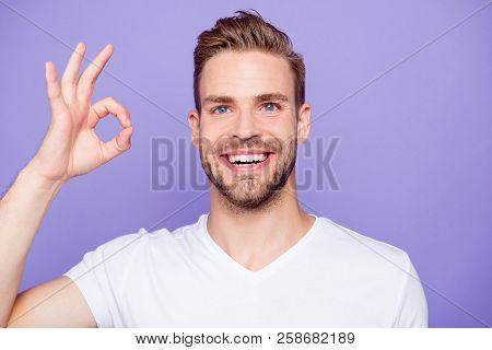 Close-up portrait of handsome cheerful attractive bearded content dreamy guy in white tshirt with stubble, bristle, showing ok-sign, isolated over pastel violet background stock photo