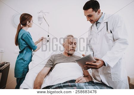 Nurse Doctor And Patiend In Clinic. Doctor And Patien. Patient And Nurse. Patiend In White Room With