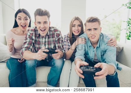 Concept of victory or defeat. Stressful match in racing or fighting a computer game, two girls support guys in a sports play stock photo