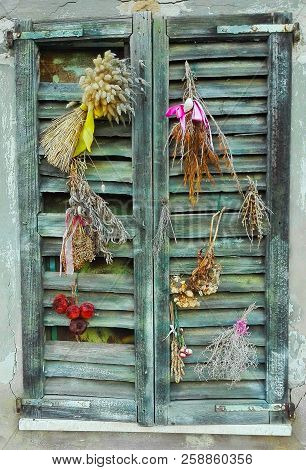 Shabby wooden window with colorful dried flowers and fruit attached above stock photo