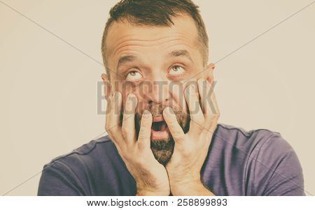 Adult man being scared and terryfied, having phobia seeing something scary. Studio shot stock photo