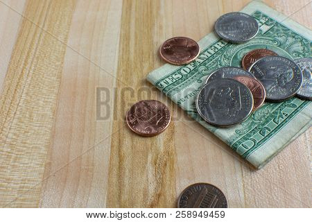 Pocket change and a folded dollar bill placed onto a wooden table. USA currency. stock photo