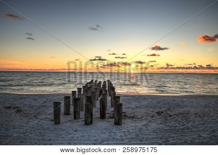 Dilapidated ruins of a pier on Port Royal Beach at sunset in Naples, Florida stock photo