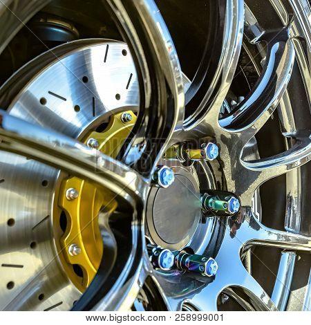 Blue bolt caps on silver rim of a car wheel stock photo