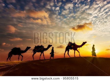 Travel background - two cameleers (camel drivers) with camels silhouettes in dunes of  desert on sunset stock photo