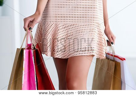 Beautiful Walking Legs Of A Woman In Dress Holding Colored Paper Bags