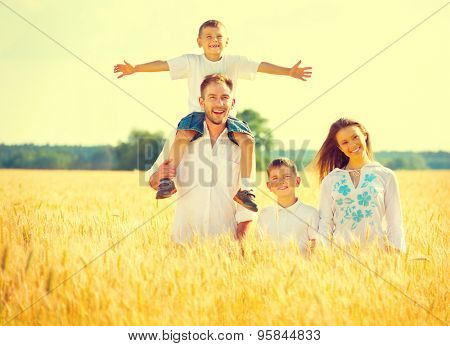 Happy Young Family with two children walking on wheat summer field. Healthy mother, father and littl