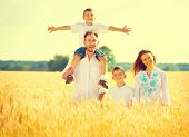 Happy Young Family with two kids strolling on wheat summer field. Solid mother, father and littl