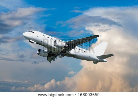 Airplane flying in the sky - travel background. Airplane closeup. Airplane flying in the colorful sunset sky. White flying airplane. Airplane in the sunlight. Closeup of flying airplane with blank livery stock photo