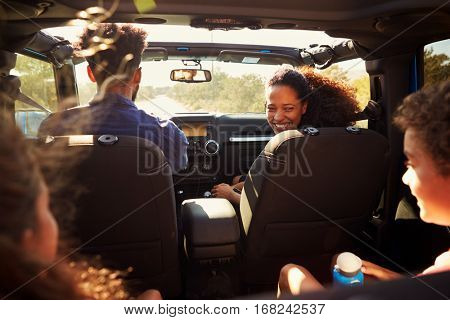 Excited family on a road trip in car, rear passenger POV