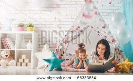 Happy loving family. Pretty young mother reading a book to her daughter indoors. Funny mom and lovel