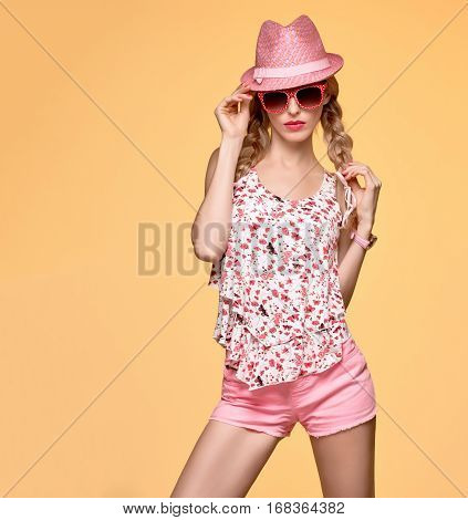 Fashion Hipster woman in Stylish Spring Summer Outfit. Cheeky emotion. Sexy Blond Model Crazy Girl, Fashion Sunglasses, Glamour Pink Shorts, Floral spring Top.Trendy pink fashion Hat.Summer Hairstyle stock photo