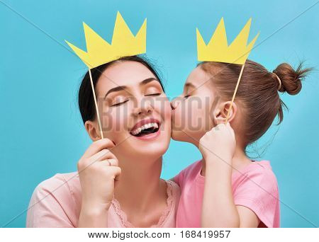 Funny family on a background of bright blue wall. Mother and her daughter girl with a paper accessor