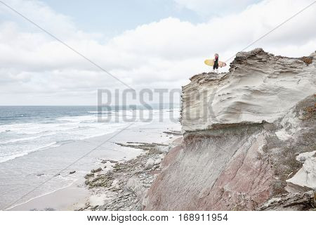 Young blonde woman wearing shorty wetsuit, standing on edge of cliff with surfboard in her hands, reading waves and preparing for surfing session - water sports concept. Baleal, Peniche, Portugal stock photo