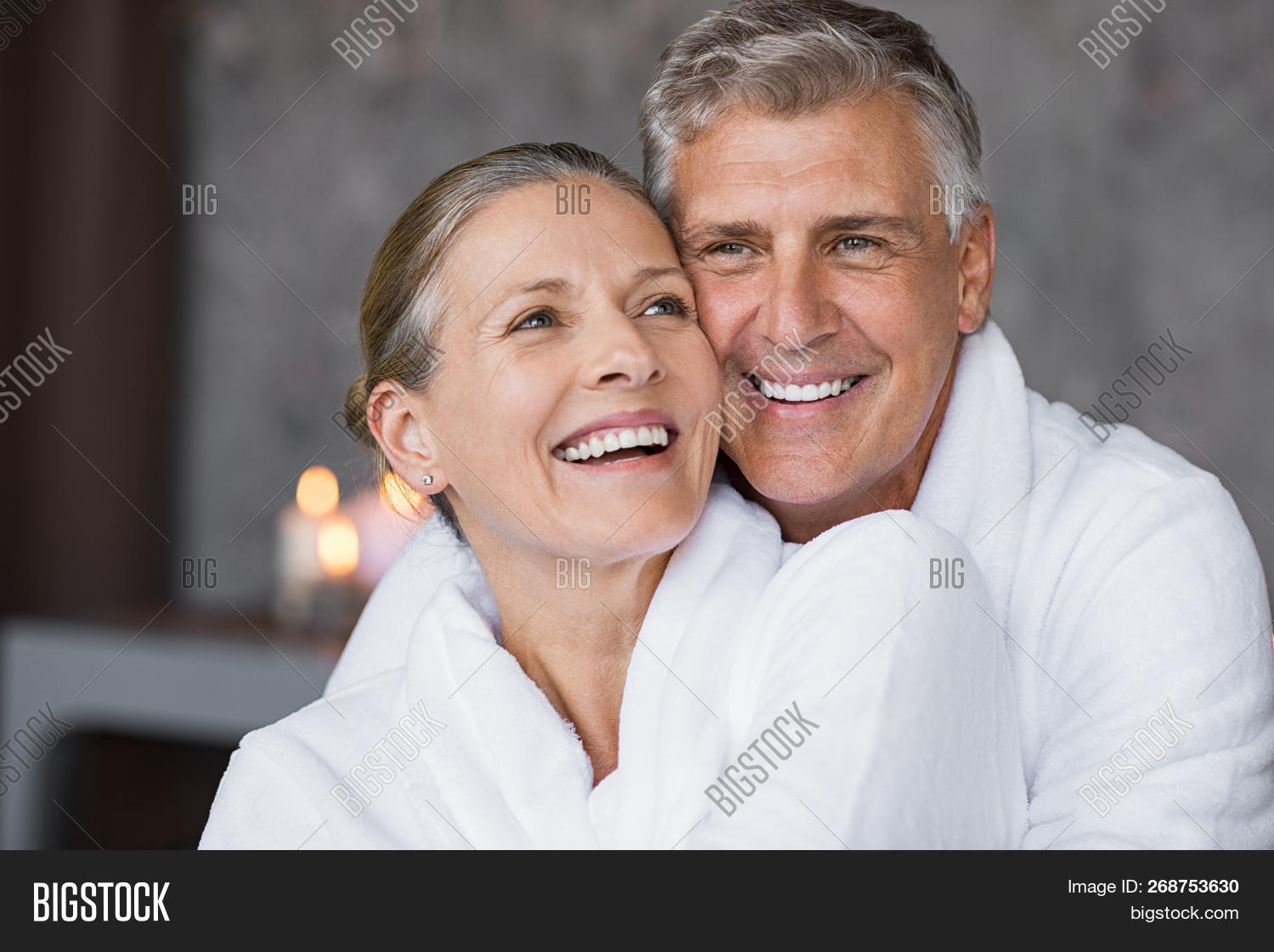 Smiling husband embracing cheerful wife from behind at spa. Laughing mature couple enjoying a romant