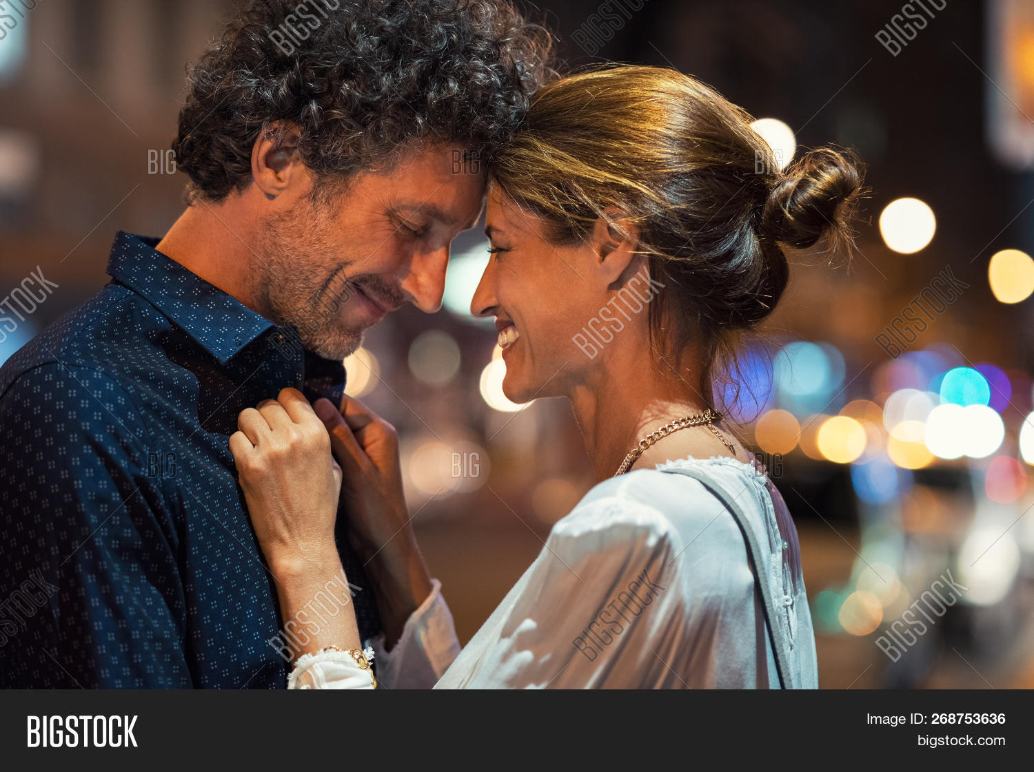 Romantic man and woman on evening date. Happy husband and smiling wife embracing touching head to he