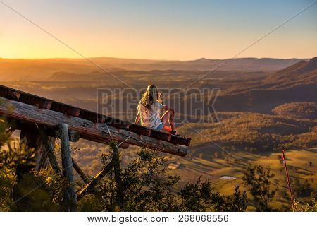 Female in casual clothes with sunlit hair flowing in the breeze relaxes on the timber platform that extends out over the valley and watches the golden sunlight fill the valley as the sun sets in the west. stock photo