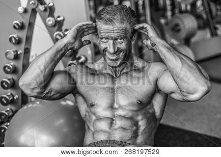 Brutal strong bodybuilder athletic aged man pumping up muscles workout bodybuilding concept background - muscular bodybuilder handsome men doing exercises in gym naked torso sport and diet concept stock photo