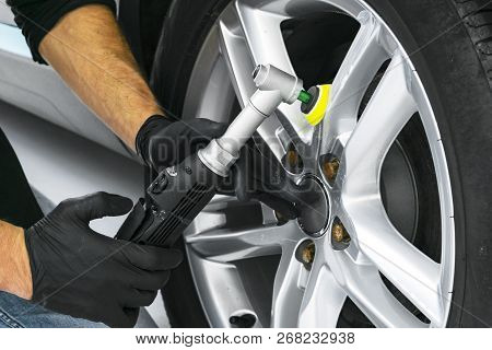 Car polish wax worker hands polishing car wheel. Buffing and polishing car disk. Car detailing. Man holds a polisher in the hand and polishes the car. Tools for polishing stock photo