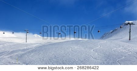 Panoramic view on gondola lift and off-piste ski slope in fog at nice sunny evening. Caucasus Mountains in winter, Georgia, region Gudauri. stock photo