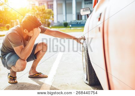 A man headache when car breakdown and wheel flat tire on the road in the city. stock photo