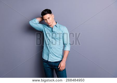 Portrait of cool cute well-groomed attractive handsome masculine man wearing blue formal shirt jeans touching hair isolated over pastel violet background stock photo