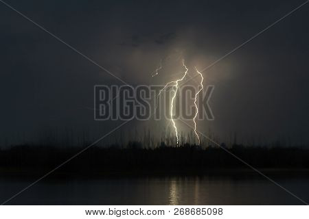 view of lightning over the lake, lightning strikes the ground, strong thunder lightning dark clouds in the sky stock photo