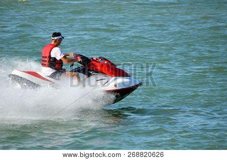 Man on a red and white jet ski speeding on the intra-coastal waterway off Miami Beach. stock photo
