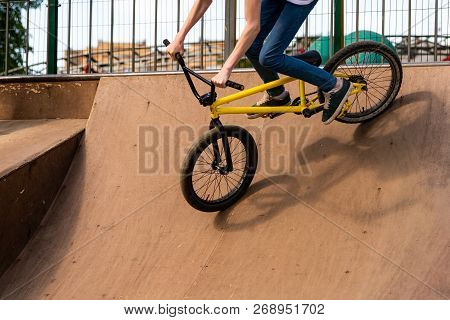 Young cyclist down the ramp. Guy is rolling down the bike from ramp. stock photo