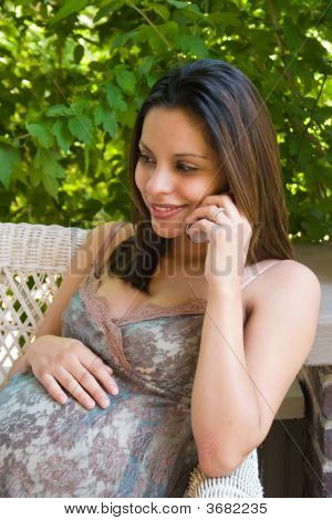 A beautiful young pregnant Hispanic woman talking on a cellphone and relaxing outside while waiting for the birth of her baby. stock photo