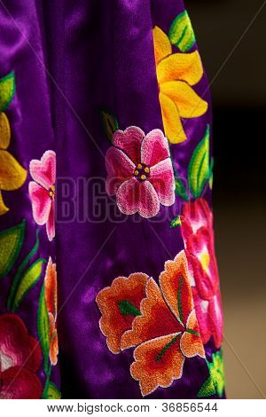 Hand-sewn mexican folkloric dress detail from Oaxaca, Mexico. This is a typical dance and ceremony regional dress. Image features selective focus con texture, leaving front and back planes out of focus for dramatic and editorial usage. stock photo