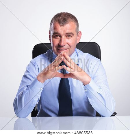 senior bussines man sitting at his office with his hands together, elbows on the table and smiling to the camera. on gray background stock photo
