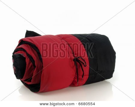 Red and black sleeping bag rolled up with bow over white stock photo