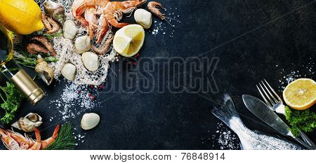 Delicious fresh fish and seafood on dark vintage background. Fish, clams and  shrimps with aromatic