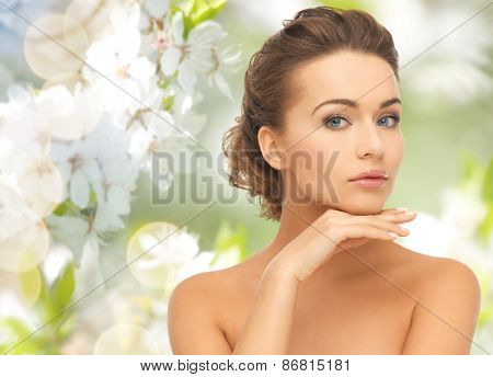 beauty, people, summer, spring and health concept - beautiful young woman touching her face over gre