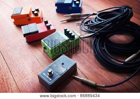 Setting up guitar audio processing effects. Electric guitar stomp box effectors and cables on studio floor. Focus is on forehand switch box. Intentionally shot with impressional feel and tone.   stock photo