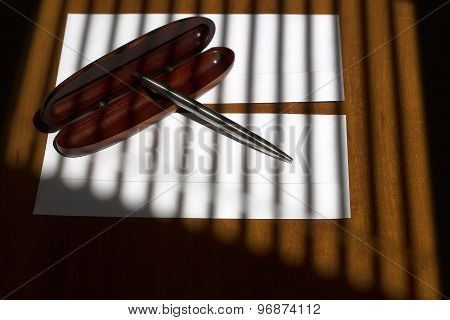 Little silver biro pen on brown wooden open case lying on two white envelopes on office table on jalousie shadow background horizontal picture stock photo