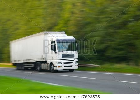 Large plain white truck with motion blur (in camera effect) stock photo
