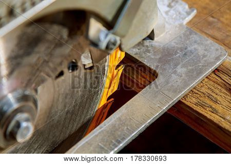 Construction worker using slider compound mitre saw or circular saw for cutting massive wood board. Details of construction renovation works stock photo