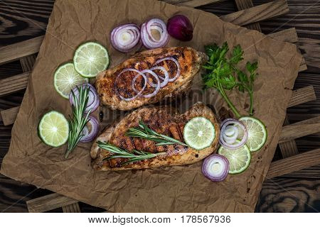 Grilled chicken filet with herbs on a paper on wooden background. Rosemary and sliced lime on a dark groundwork. stock photo