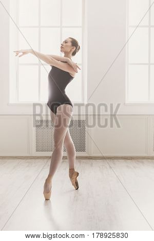 Classical Ballet dancer training. Beautiful graceful ballerina in black practice ballet positions near large window in light hall. Ballet class training, high-key soft toning. Vertical image
