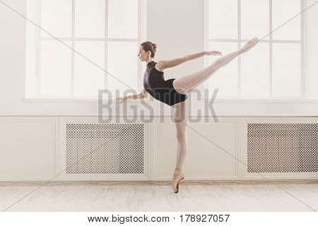 Classical Ballet dancer in arabesque position in light hall. Ballerina training, high-key soft toning.
