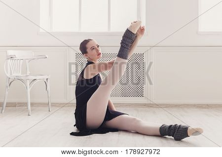 Classical Ballet dancer stretching. Beautiful graceful ballerina in black practice at ballet class training, high-key soft toning.