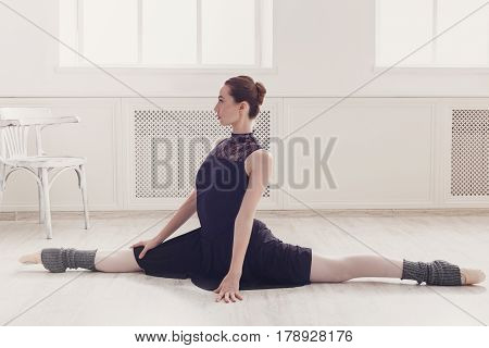 Classical Ballet dancer in split position in class room background. Ballerina training, high-key soft toning.