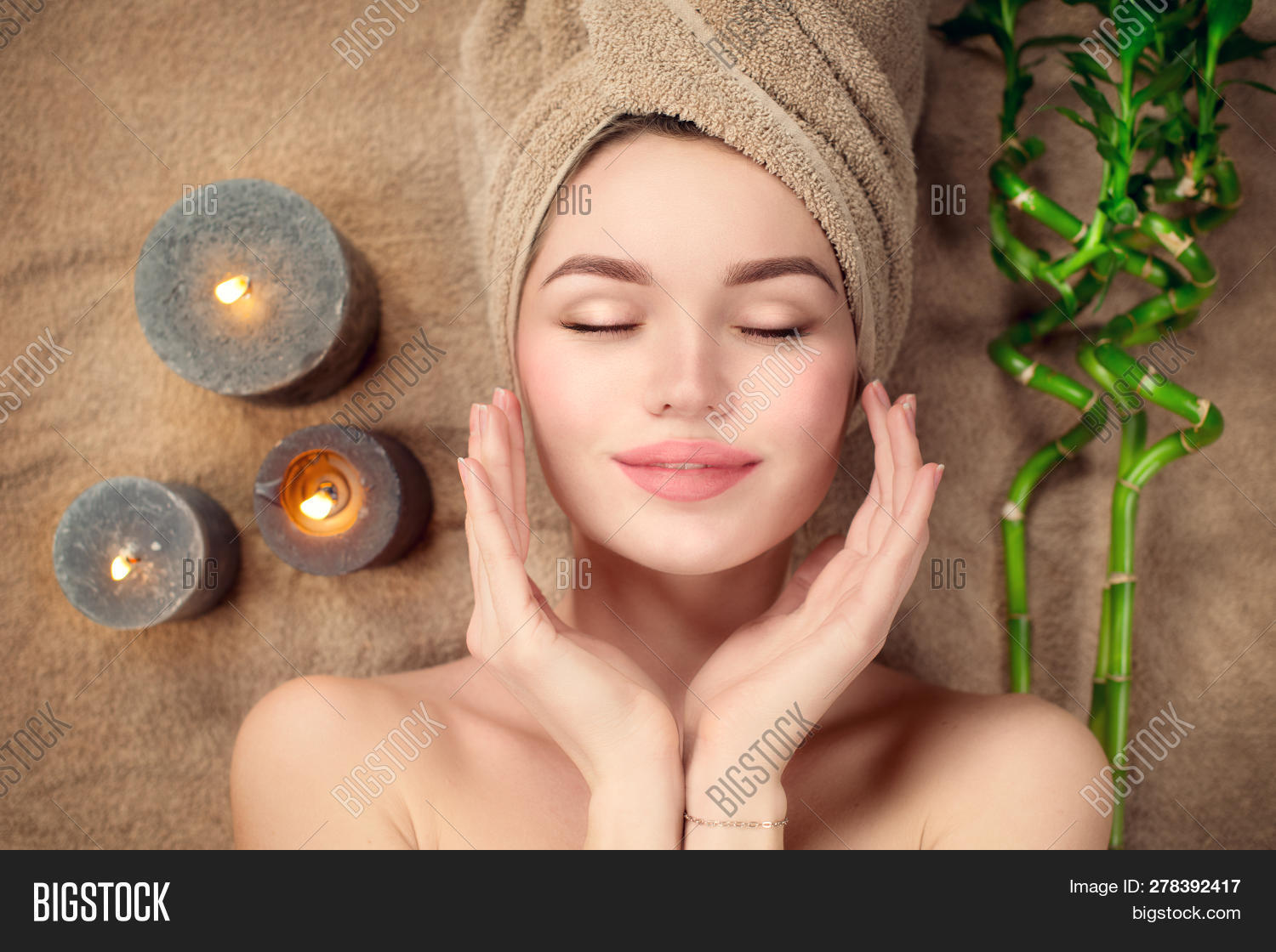 Beautiful spa woman with a towel on her head lying and touching face skin. Skincare. Beauty smiling