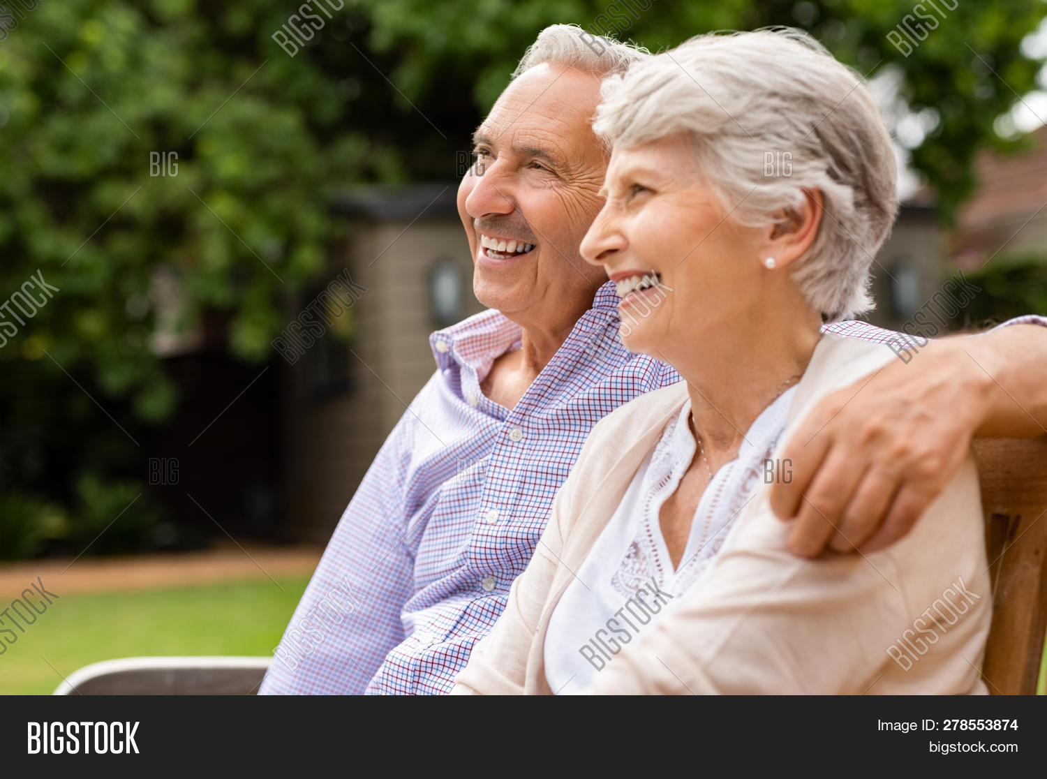 Senior couple sitting together on bench at park. Elderly married couple sitting outdoor and relaxing