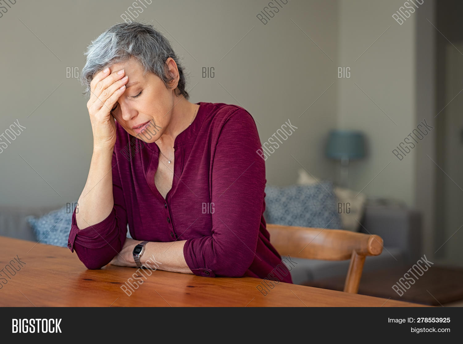 Senior woman suffering from headache while sitting at table in a living room. Depressed mature woman