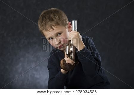 Boy with a gun. The child plays with the weapon. Six seven year old toddler with retro boob stock photo